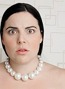 Young plus-size woman wearing pearl necklace, portrait, close-up