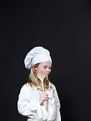 Girl 6-8 dressed as chef holding wooden spoon to cheek
