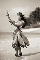 Beautiful Hawaiian woman dancing hula on ocean shoreline black and white photograph