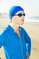 Mature woman wearing headphones at beach