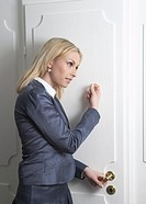Young businesswoman knocking on door