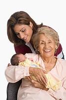Grandmother posing with daughter and newborn grandchild