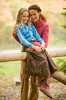 Mother and daughter smiling by wooden gate