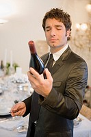 Man examining bottle of wine (thumbnail)