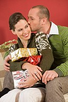 Woman holding stack of gifts from boyfriend