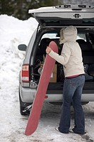 Young woman unloading a snowboard from her trunk