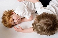 Two three-year-old boys lying down and talking.