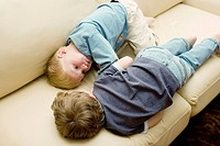 Two four-year-old boys lying down and talking