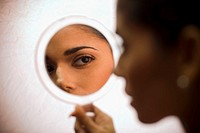 Young woman looking in handheld mirror