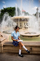 School girl sitting in center plaza by fountain