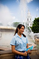 School girl in center plaza by fountain