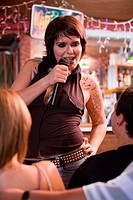 Young woman with tatoos singing at bar
