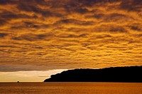 Fishing boat on lake with fire gold clouds at sunup
