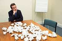 Young businessman struggling with paperwork.