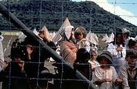 Film,Eine Frau wie Tausend Feuer,Regie: Dirk De Villiers,USA,1992, Filmszene mit: NIP Menschen hinter Zaun