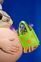 Pregnant woman holding a bag with flowers and touching her stomach, midsection