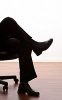 Legs of a business person sitting on an office chair