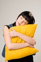 Woman hugging cushion with eyes closed (thumbnail)