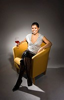 Woman sitting on sofa holding a glass of red wine (thumbnail)