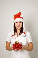 Female doctor with santa hat holding present
