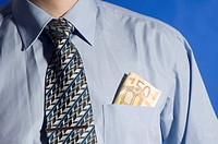 Businessman with money in his shirt pocket, midsection