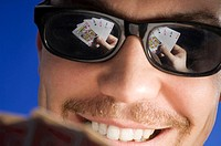 Closeup of man playing poker with reflection through his sunglasses
