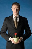 Businessman holding cactus in a pot with closed eyes