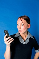 Woman staring shockingly at her mobile phone