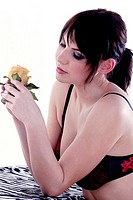 Woman in black and red lingerie looking at flower
