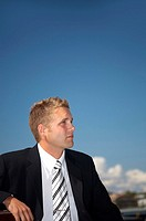 Businessman sitting outdoors, looking away