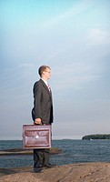 Businessman carrying briefcase while looking away