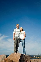 Couple standing on the rock enjoying the seaview