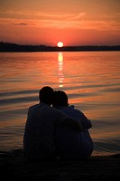 Romantic couple watching sunset at the beach