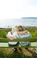 Couple sitting on the bench enjoying the seaview