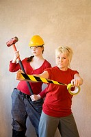 Women posing with sledge hammer and adhesive tape