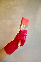 Hand in rubber glove holding paint brush