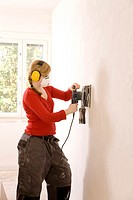 Woman steam-stripping the wallpaper