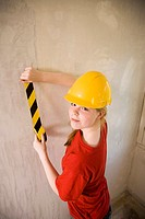 Teenage girl taping adhesive tape on the wall