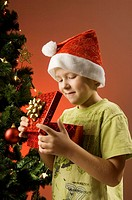 Boy with santa hat looking into a gift box