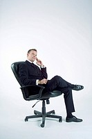 Businessman sitting on office chair, thinking (thumbnail)