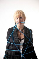 Tied up businesswoman biting on rope (thumbnail)