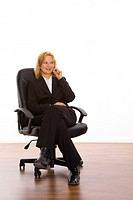 Businesswoman sitting on office chair talking on the mobile
