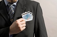 Midsection of businessman taking money from his blazer pocket