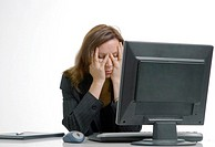 Businesswoman with hands covering her face, in front of desktop