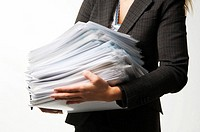 Businesswoman balancing a stack of paperwork, midsection
