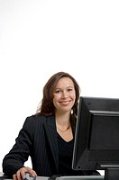 Businesswoman working in front of her desktop while posing for the camera