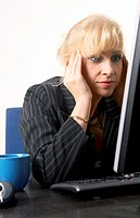Businesswoman staring at her desktop monitor with hands on her temples