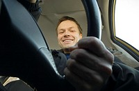 Man smiling at the camera while driving in the car