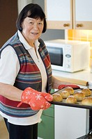 Senior woman with a tray of freshly baked buns (thumbnail)
