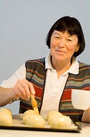 Senior woman brushing buns with egg yolk